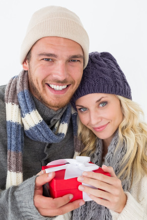 Attractive young couple in warm clothing holding gift over white background photo