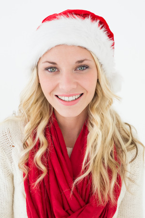 Portrait of attractive young woman wearing santa hat over white background photo