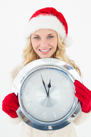 Portrait of attractive santa woman holding clock over white background photo