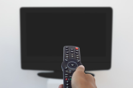 changing channel: Close up of hand holding remote and changing channel Stock Photo