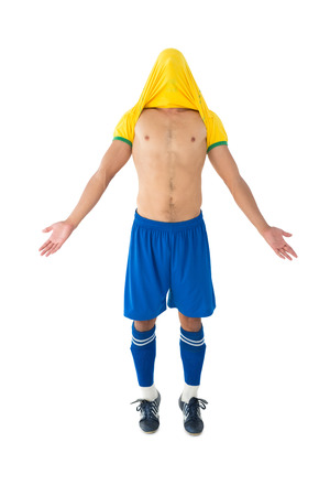 player: Full length of fit football player cheering over white background