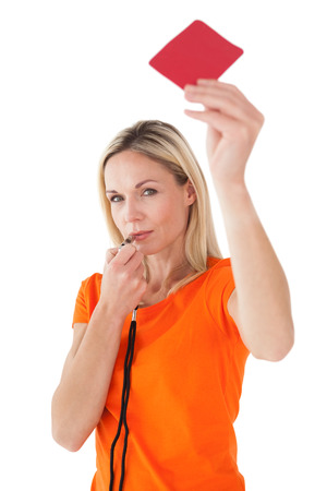Portrait of mature woman blowing whistle and holding red card on white background photo