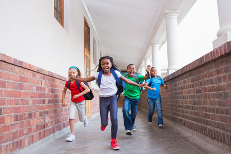 elementary school: Cute pupils running and smiling at camera in hallway at the elementary school Stock Photo