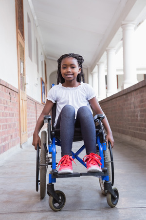 paraplegic: Cute disabled pupil smiling at camera in hall at the elementary school Stock Photo
