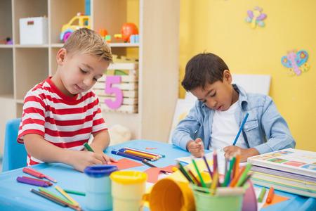 保育園の教室で一緒にアートを作るかわいい男の子