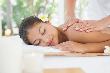 Beautiful brunette enjoying a massage at the health spa photo