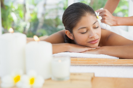 Beautiful brunette enjoying a herbal compress massage at the health spa photo