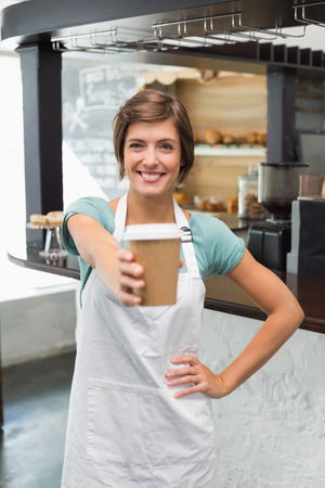 Pretty barista smiling at camera holding disposable cup at the coffee shop photo
