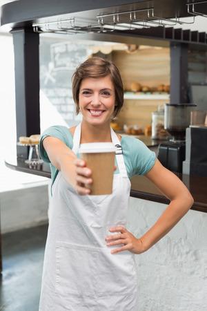 taza de t�: Sonriendo a la c�mara sosteniendo vaso desechable en la cafeter�a Pretty barista Foto de archivo