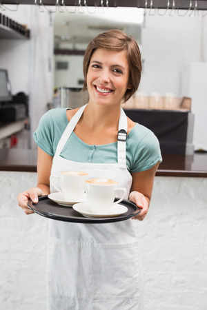 Waitress holding tray with cappuccinos at the coffee shop photo