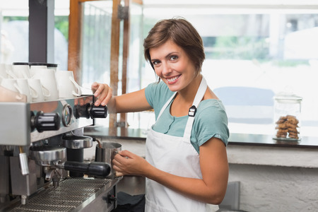 Pretty barista steaming jug of milk at coffee machine at the coffee shop photo