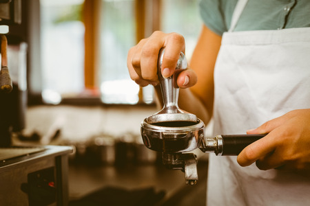 Barista pressing fresh coffee grinds at the coffee shop photo