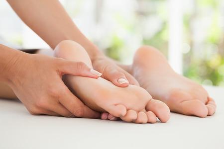 Mujer que recibe un masaje de pies en el spa de salud Foto de archivo