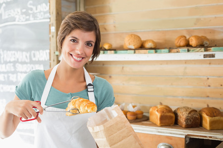 Pretty waitress picking up croissant at the coffee shop photo
