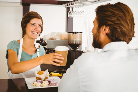 Pretty waitress serving happy customer at the coffee shop photo