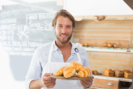 Handsome waiter holding tray of croissants at the coffee shop photo