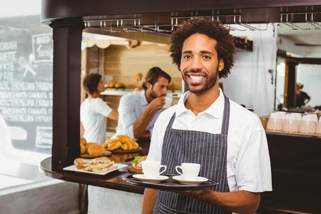 Handsome Kellner l�chelt in die Kamera h�lt Tablett in der Cafeteria Lizenzfreie Bilder