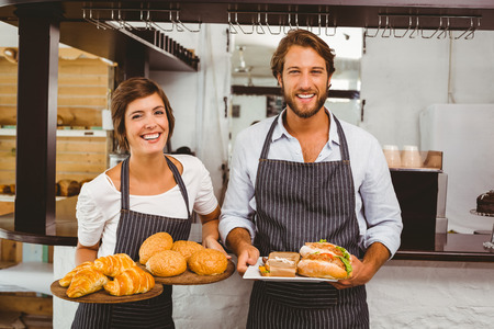 Happy servers holding plates of food at the coffee shop