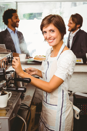 Pretty barista making cup of coffee at the coffee shop photo