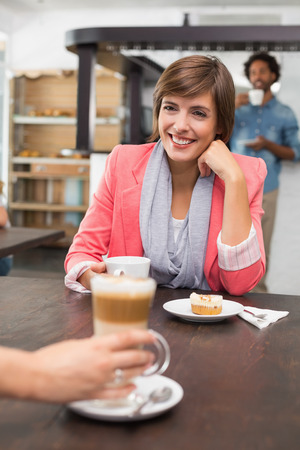 Pretty brunette enjoying her latte with a friend at the coffee shop photo
