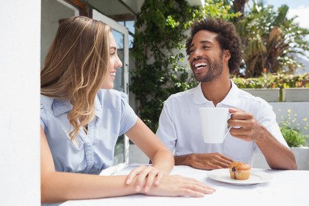 Happy couple having coffee together outside at the coffee shop photo