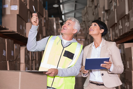Pretty warehouse manager talking to foreman in a large warehouse photo