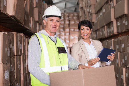 Warehouse worker moving boxes on trolley talking to manager in a large warehouse photo