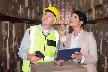 Warehouse worker scanning box with manager in a large warehouse