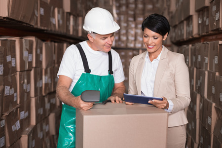 warehouse worker: Warehouse worker scanning box with manager holding tablet pc in a large warehouse