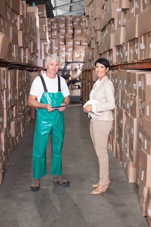 Warehouse worker and manager smiling at camera in a large warehouse photo