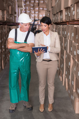 Warehouse worker and manager using tablet pc in a large warehouse photo