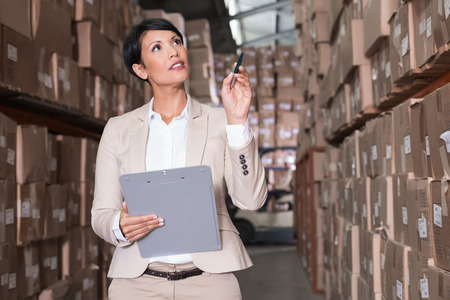 Warehouse manager checking her inventory in a large warehouse Stok Fotoğraf
