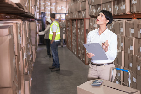 Pretty warehouse manager checking inventory in a large warehouse photo