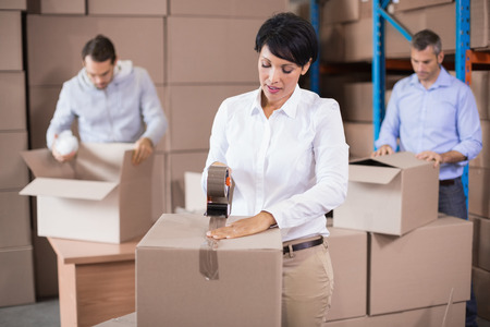shutting: Warehouse workers packing up boxes in a large warehouse Stock Photo