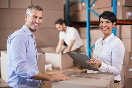 warehouse: Warehouse manager writing on clipboard talking to colleague in a large warehouse Stock Photo