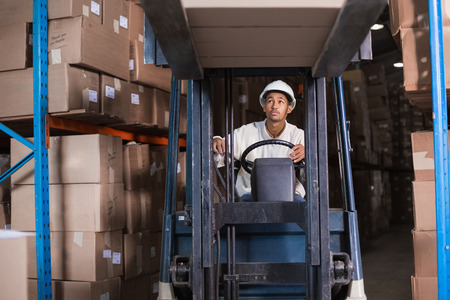 forklift driver: Forklift driver operating the machine in a large warehouse
