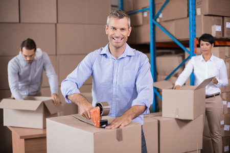 packing boxes: Warehouse workers packing up boxes in a large warehouse Stock Photo