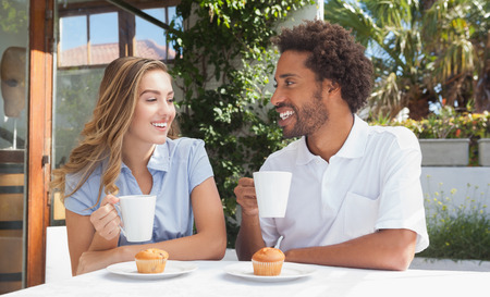 18 to 30s: Happy friends having coffee together outside at the coffee shop
