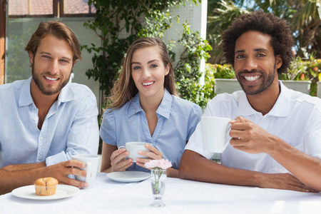 18 to 30s: Happy friends enjoying coffee together outside at the coffee shop Stock Photo