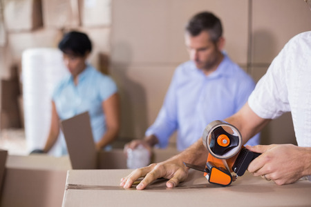 sealing tape: Warehouse workers preparing a shipment in a large warehouse