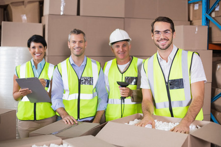 packing boxes: Warehouse workers in yellow vests preparing a shipment in a large warehouse Stock Photo