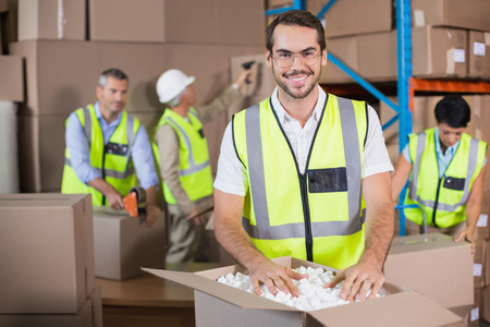 warehouse: Warehouse workers in yellow vests preparing a shipment in a large warehouse Stock Photo