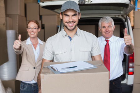 Warehouse managers and delivery driver smiling at camera in a large warehouse photo