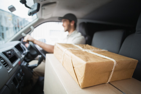 driving: Delivery driver driving van with parcels on seat outside the warehouse Stock Photo