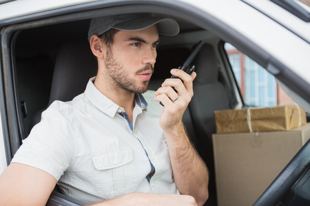Delivery driver talking on walkie talkie in his van outside the warehouse Stock Photo