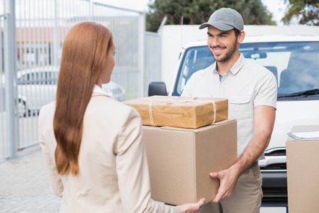 warehouse: Delivery driver passing parcels to happy customer outside the warehouse Stock Photo