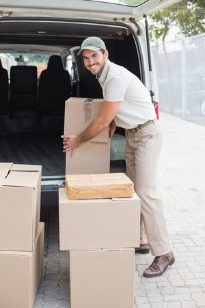 delivery driver: Delivery driver loading his van with boxes outside the warehouse Stock Photo