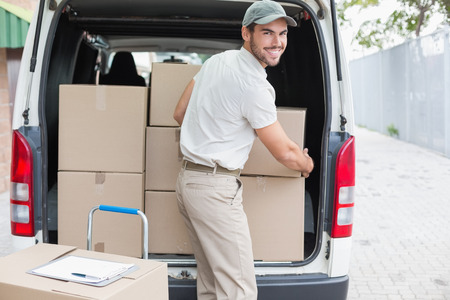 van: Delivery driver loading his van with boxes outside the warehouse Stock Photo