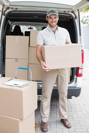 Livreur chargement de sa camionnette avec des boîtes à l'extérieur de l'entrepôt