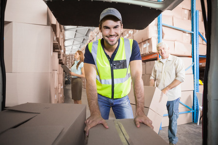 freight transportation: Delivery driver loading his van with boxes outside the warehouse Stock Photo